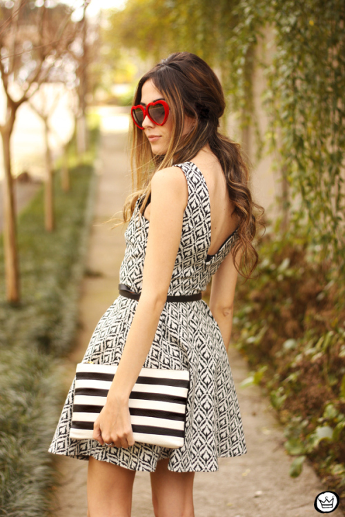 Flávia Desgranges is wearing a print dress from Fabrique, sunglasses from NastyGal and a striped clutch from Dafiti