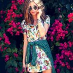 TJ Wallace wearing a tropical print dress from Nasty Gal