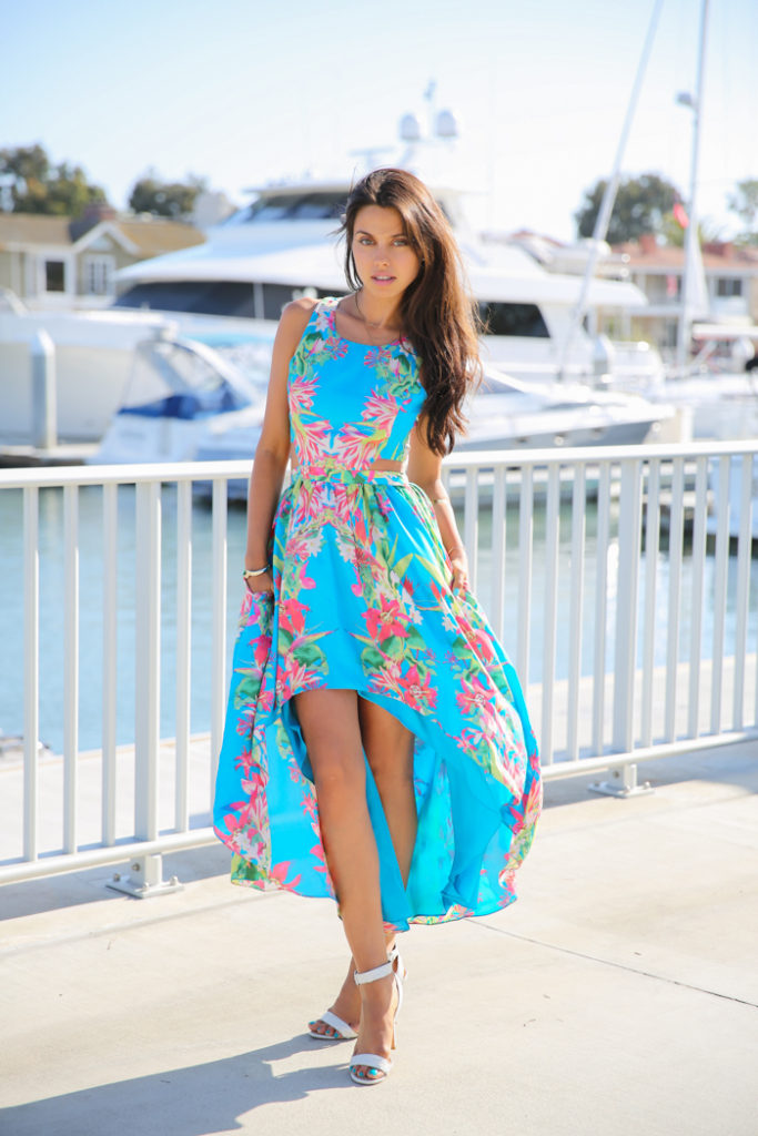 Annabelle Fleur is wearing an asymmetrical tropical dress from Lovers And Friends and white sandals from Coach Leighann
