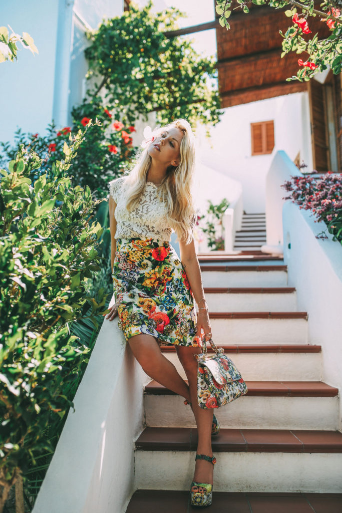 Shea Marie is wearing a white lace top and tropical print skirt, shoes and bag all from Dolce & Gabbana