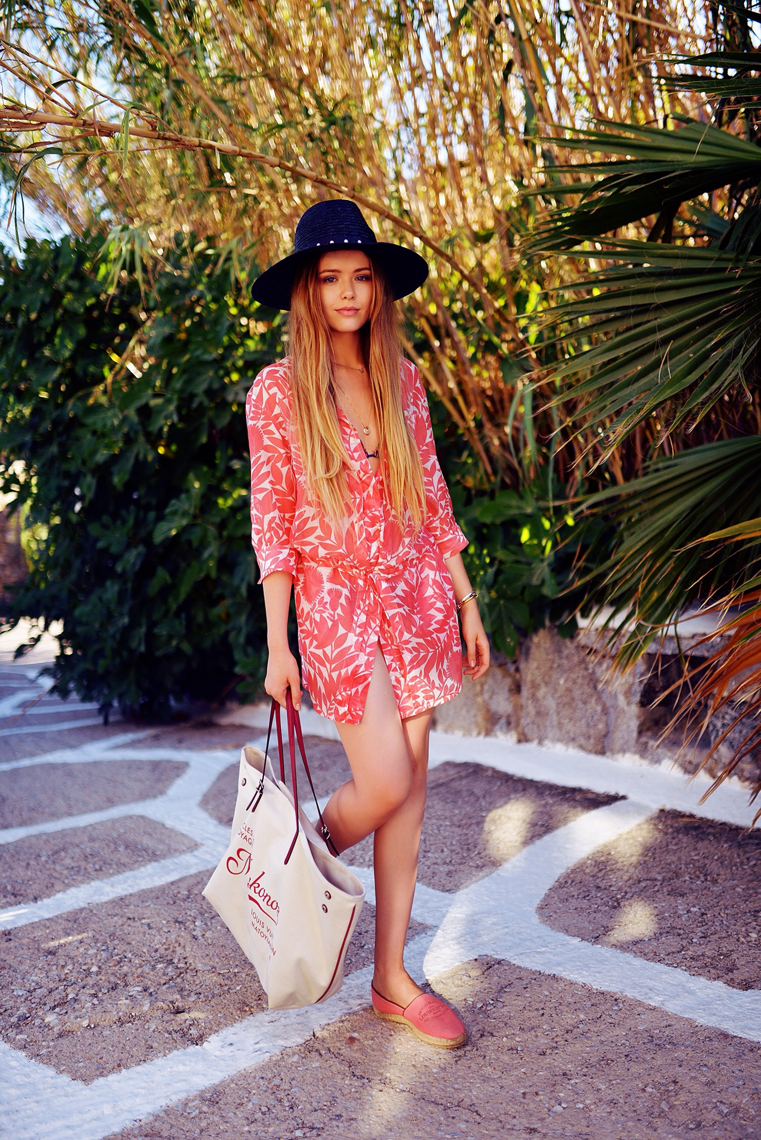 Kristina Bazan is wearing a red and white tropical dress and shoes from Louis Vuitton and a hat from The Kooples