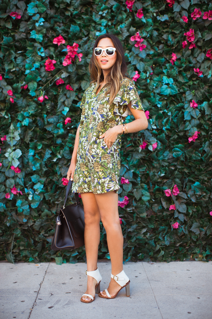 Aimee Song is wearing a tropical print linen dress from Minusey, sunglasses from Seneca, shoes and bag from Celine