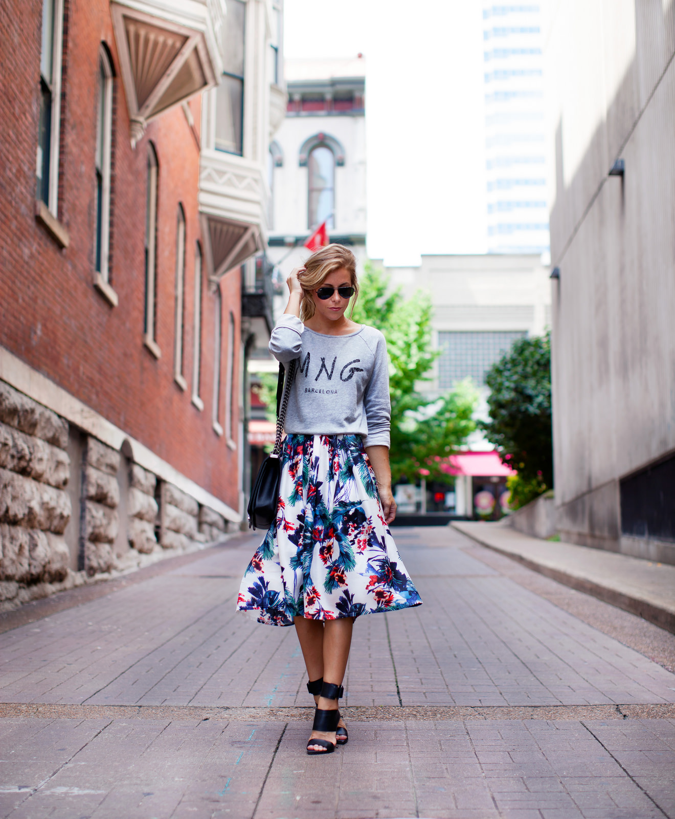 Mary Seng is wearing a logo sweatshirt from Mango, tropical midi skirt from Chicwish, shoes from Tibi and the bag is from Chanel