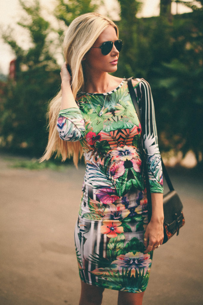Amber Fillerup Clark is wearing a tropical dress from TopShop, sunglasses from RayBan and the bag is from Vince Camuto