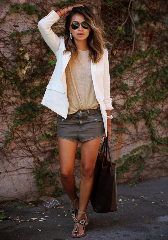 Julie Sarinana is wearing a short shorts from Urban Outfitters, T-shirt from Acne Studios, white blazer from H&M and sandals from Isabel Marant
