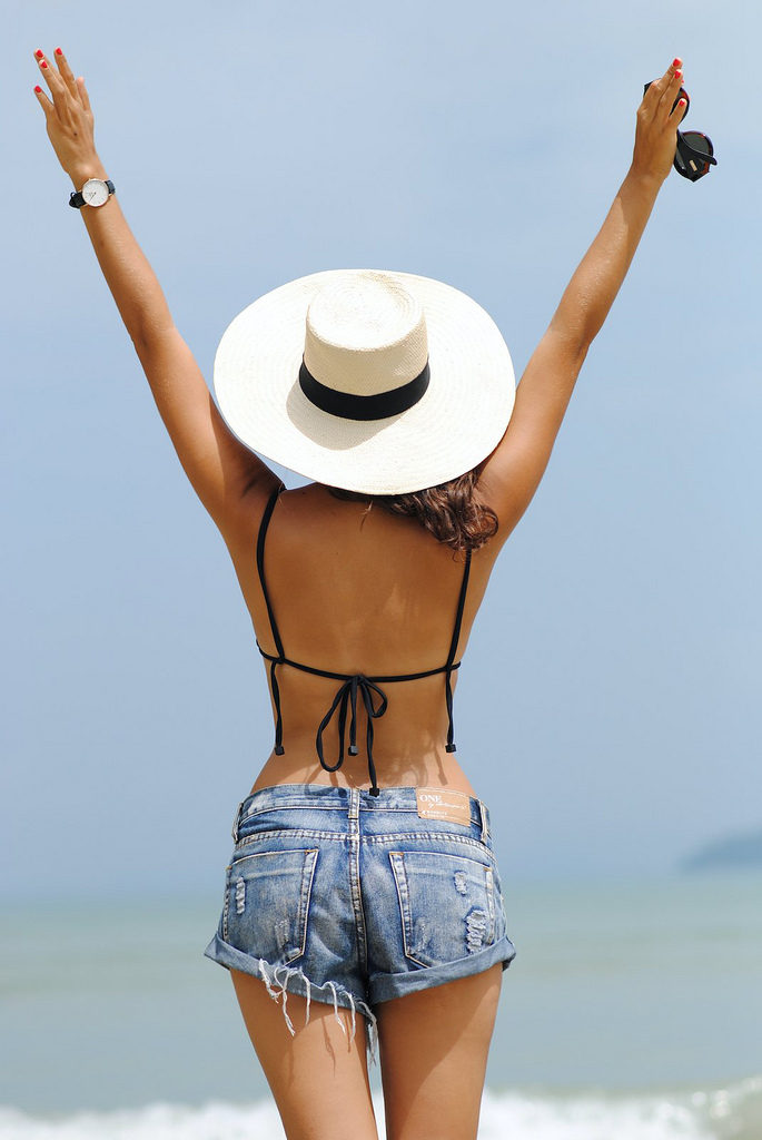 Geneva Vanderzeil is wearing denim shorts from One Teaspoon, black bikini top from Triangl and a Panama hat from J. Crew
