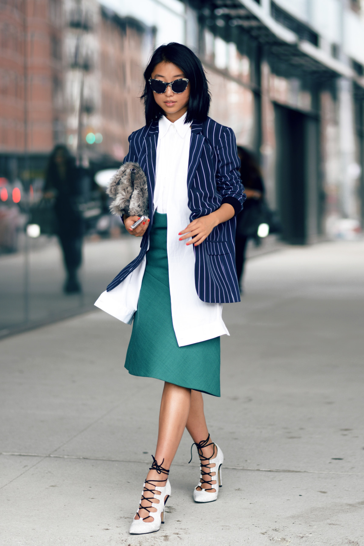 Margaret Zhang is wearing a pinstripe blazer from Tibi, shirt from Dion Lee, wool skirt from Jil Sander, bag from Elizabeth and James, sunglasses from Illesteva Claire and white lace up shoes from Mode Collective