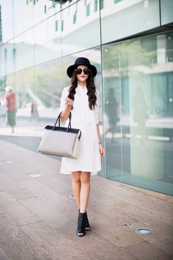 Rachel Parcell is wearing a shirt dress from 3.1 Phillip Lim, hat from Rag and Bone, boots from Vince, bag from Tiffany & Co. and sunglasses from Karen Walker