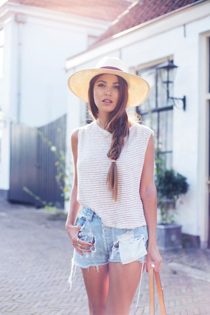 Negin Mirsalehi is wearing a striped top from Monki, a panama hat from Nasty Gal and denim shorts from Levi's
