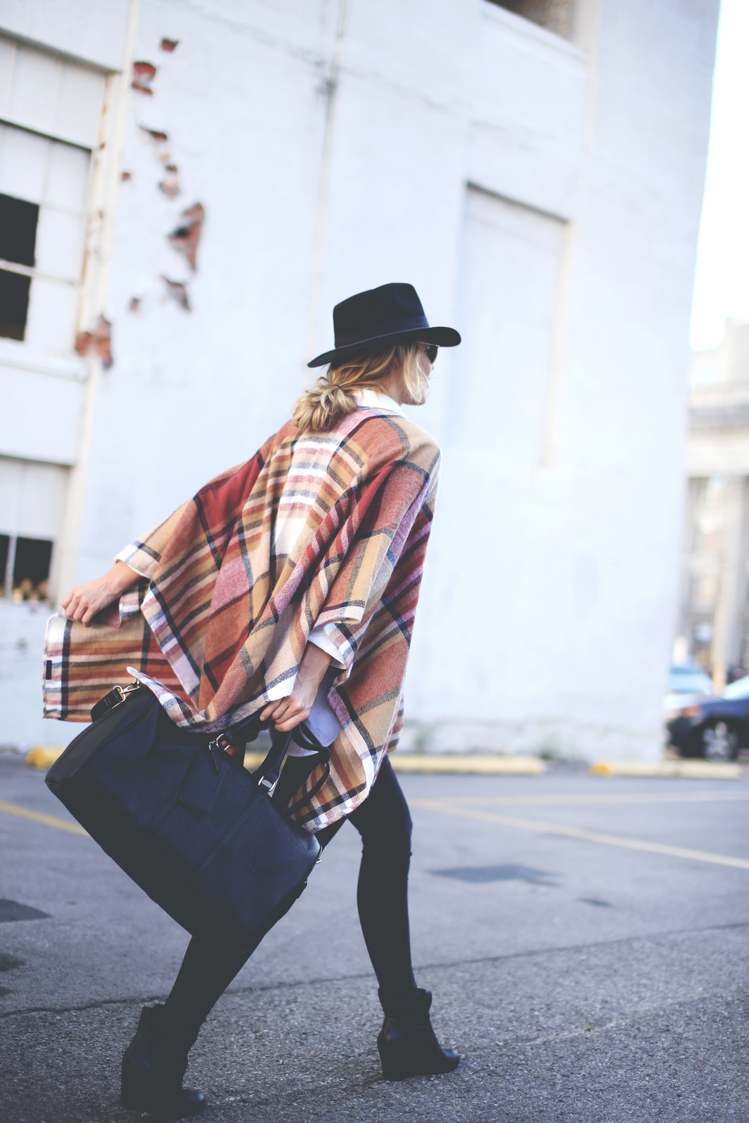 Mary Seng is wearing a plaid cape from TopShop, jeans from J Brand, bag and boots from Sole Society and the hat is from Madewell