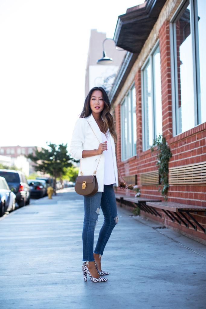 Aimee Song is wearing a white double breasted blazer from Mango, distressed jeans from J Brand, shoes from Nicholas and the bag is from Chloe