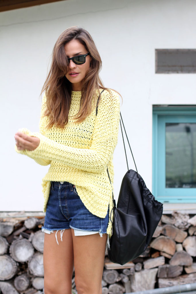 Silvia Zamora is wearing a yellow knit jumper from Zara, vintage denim shorts from Levi's and a backpack from Rembs Rita