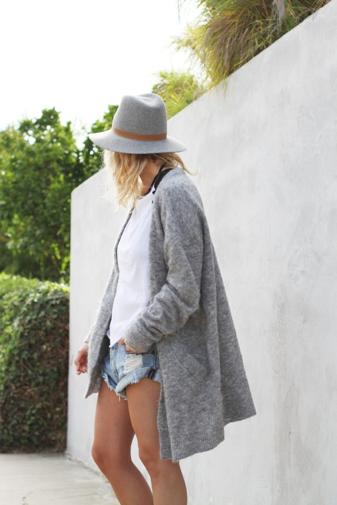 Mija is wearing a mohair knit cardigan from Acne Studios, long sleeve white top from TopShop and denim shorts from One Teaspoon