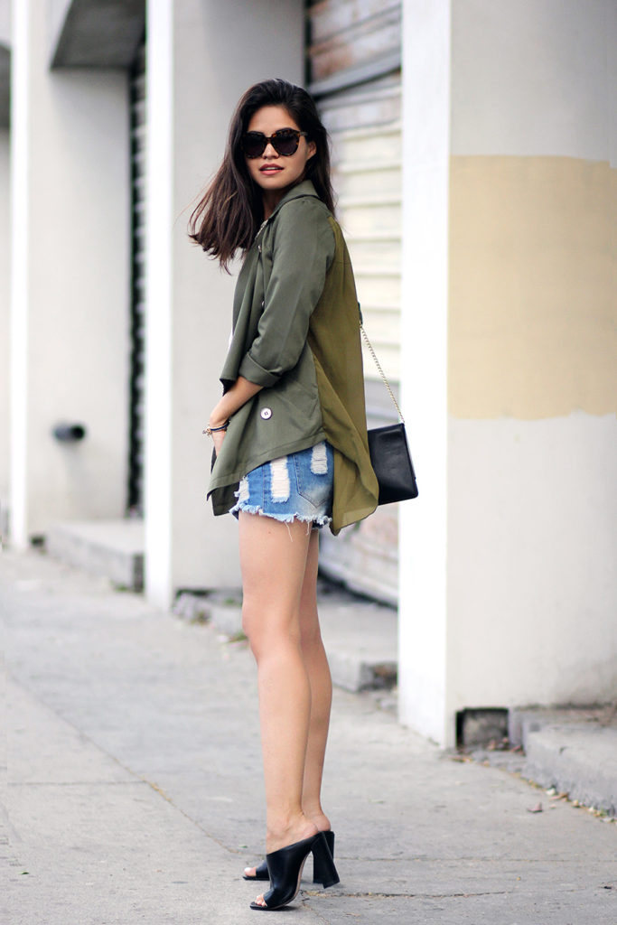 Adriana Gastélum is wearing a military green jacket from SheInside, denim shorts from Forever21 and mules from Zara