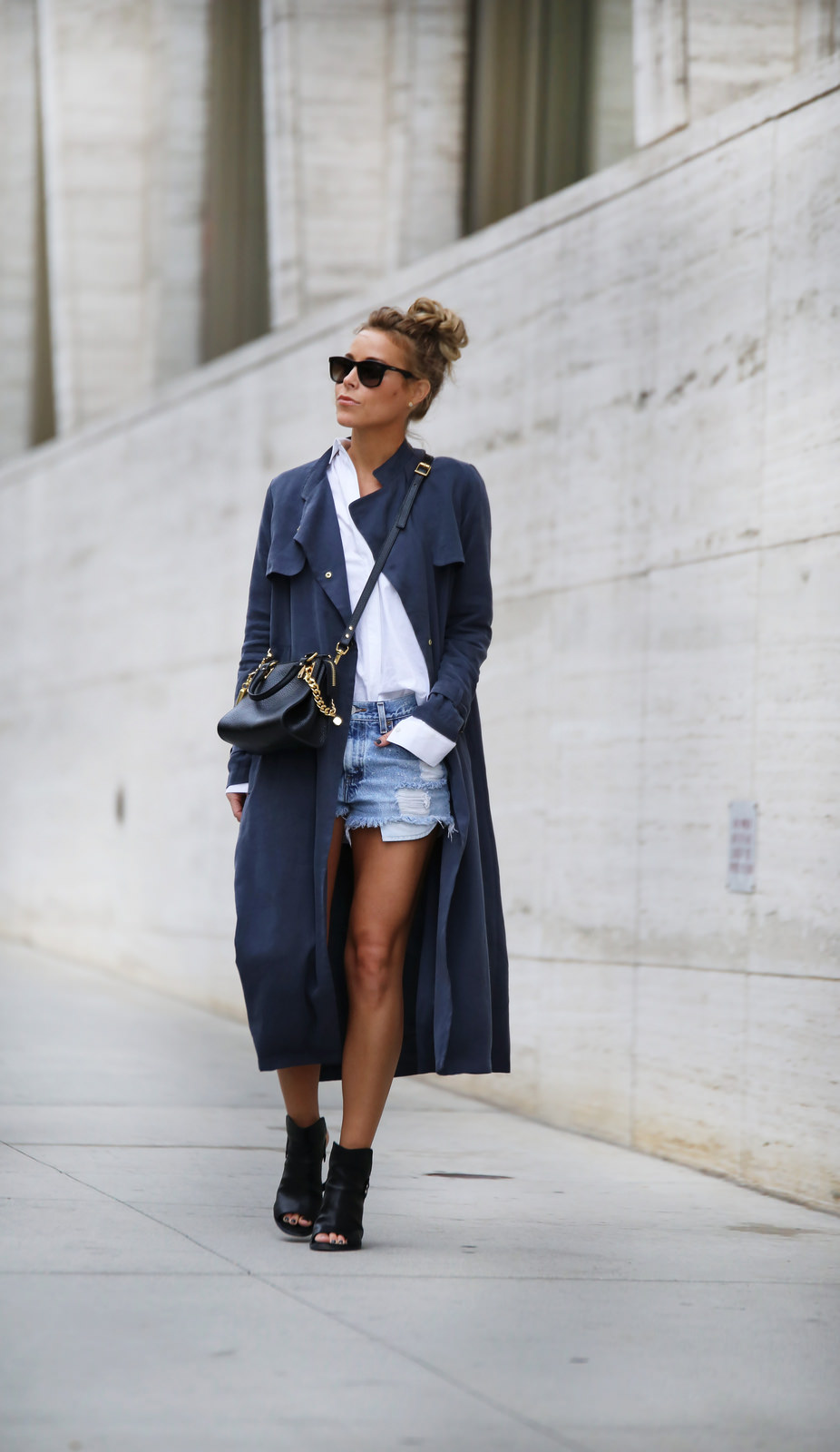 Mary Seng is wearing a blue duster from French Connection, white shirt from Alexander Wang, denim shorts from Levi's, sandals from Rag & Bone and the bag is from Sophie Hulme