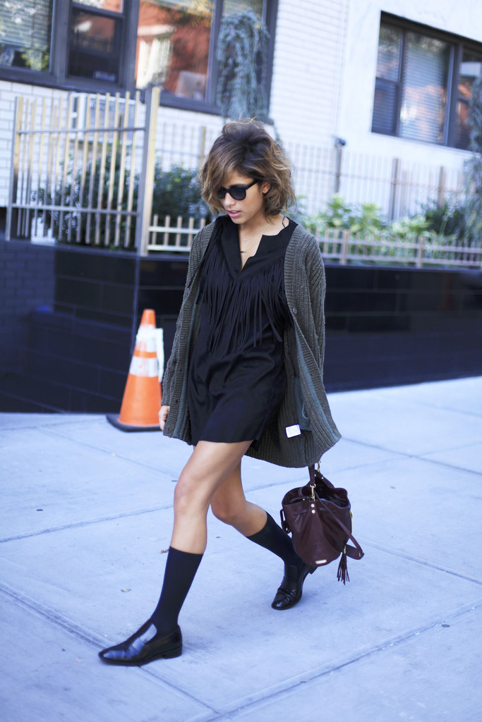 Christina Caradona is wearing a black fringe dress, cardigan from Aritzia, shoes from & Other Stories and a bag from Elizabeth & James
