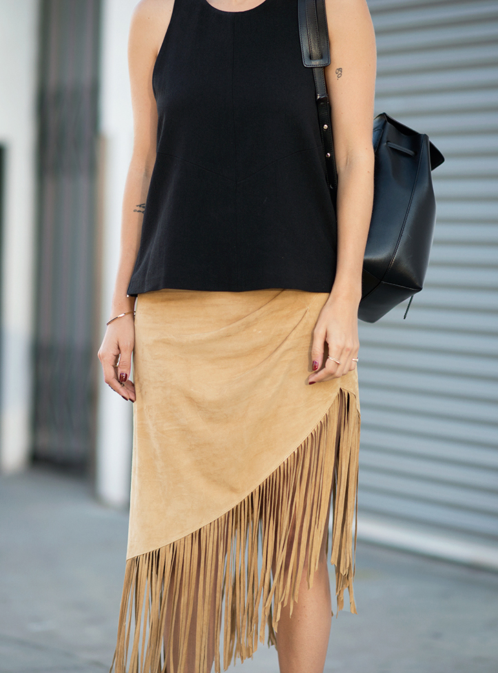 Courtney Trop is wearing a black size zip tank from Iro and the Seneca fringe skirt is from Cheyann Benedict