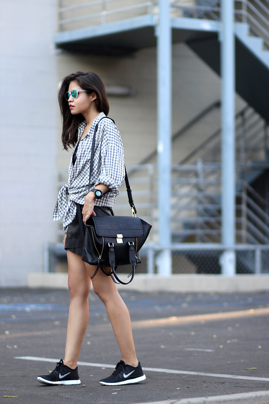 Adriana Gastélum is wearing a gingham shirt from Young Hungry Free, crop top from Zara, black skirt from Maje, bag from 3.1 Phillip Lim, mirrored sunglasses from Hawckers and the sneakers are from Nike