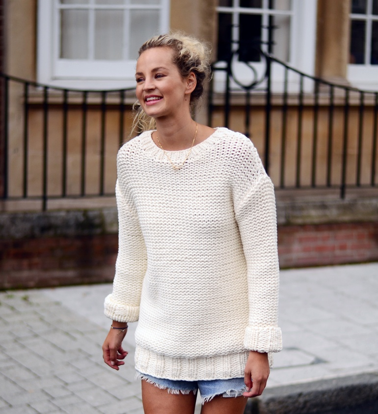 Anouk Yve is wearing a denim shorts from Levis and a white knitwear jumper from & other stories