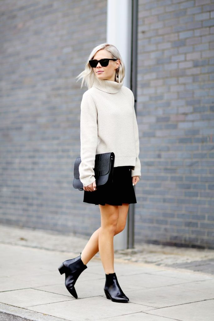 Jessie Bush is wearing sunglasses from Nick Campbell, oversized jumper from Proenza Schouler, skirt from Uniform Studios skirt, clutch from Danielle Foster and the boots are from Saint Laurent