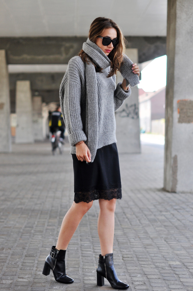 Kelly Elise is wearing a grey knitted sweater and scarf from Closed, skirt from Vanilia, shoes from Prada and sunglasses from Anine Bing