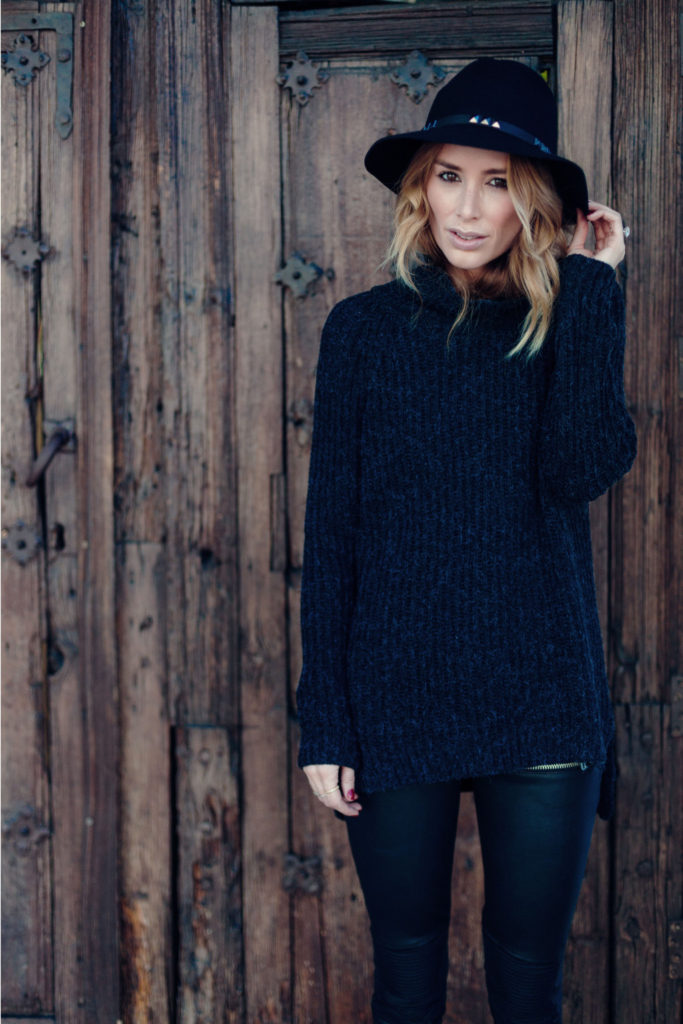 Anine Bing is wearing a charcoal turtleneck knit sweater from Anine Bing