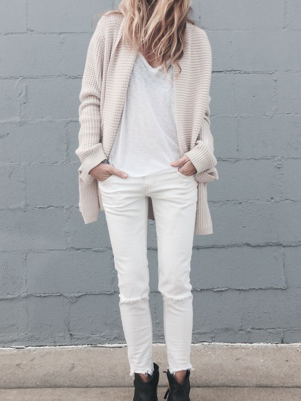 Laura Wiertzema is wearing a white heavy knit cardigan
