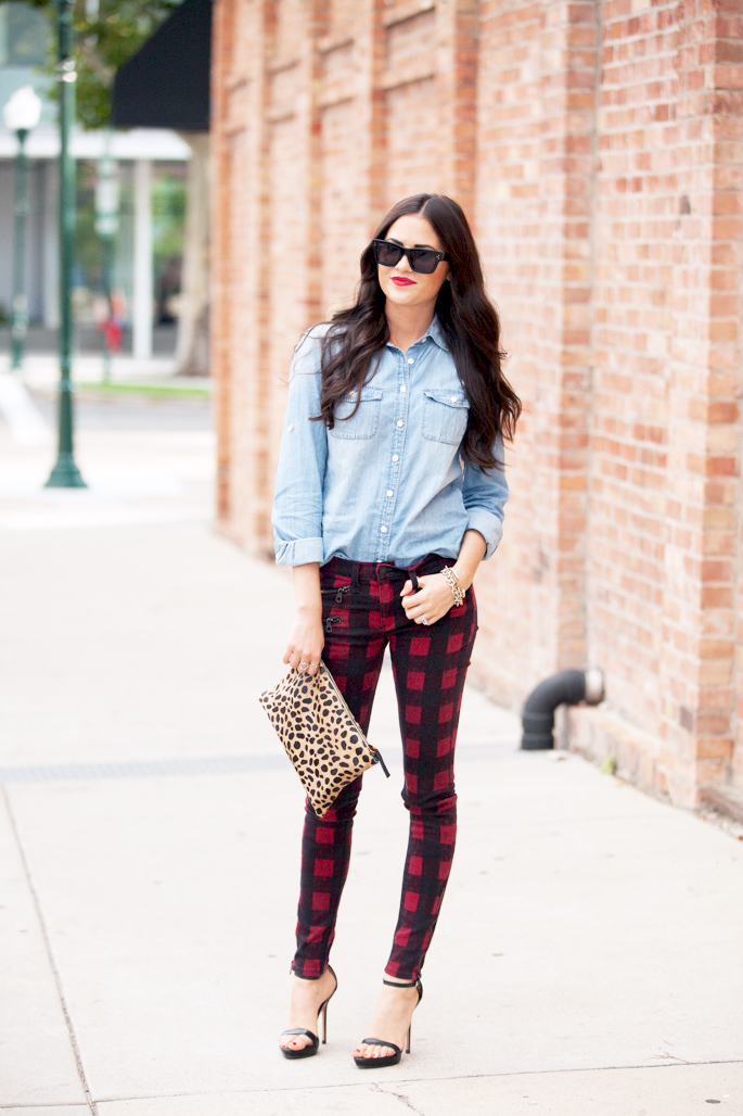 Rachel Parcell is wearing a denim shirt from J.Crew, print denim leggings from Rag & Bone, leopard print Clutch from Clare Vivier and shoes from Zara