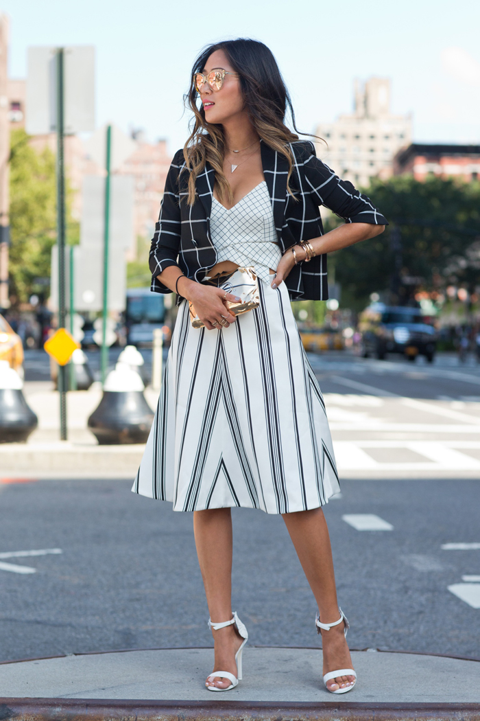 Aimee Song is wearing a checked print crop top from Keepsake, high waisted striped midi skirt from Cameo and a plaid blazer from Express