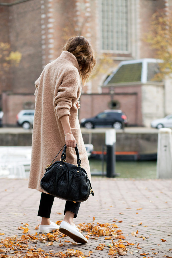 Christine R. is wearing an oversized woolen wrap camel coat from Ganni