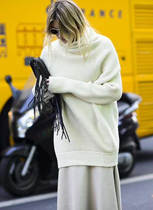 Camille Charriere is wearing a white oversized knit top from ACNE, grey skirt from Chloe and the fringed clutch is from By Malene Birger