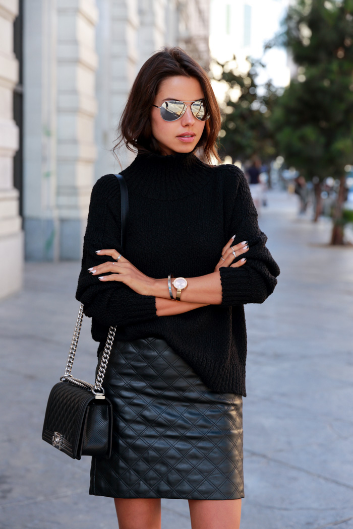 Annabelle Fleur is wearing a black faux quilted leather skirt and turtleneck from Banana Republic and a bag from Chanel