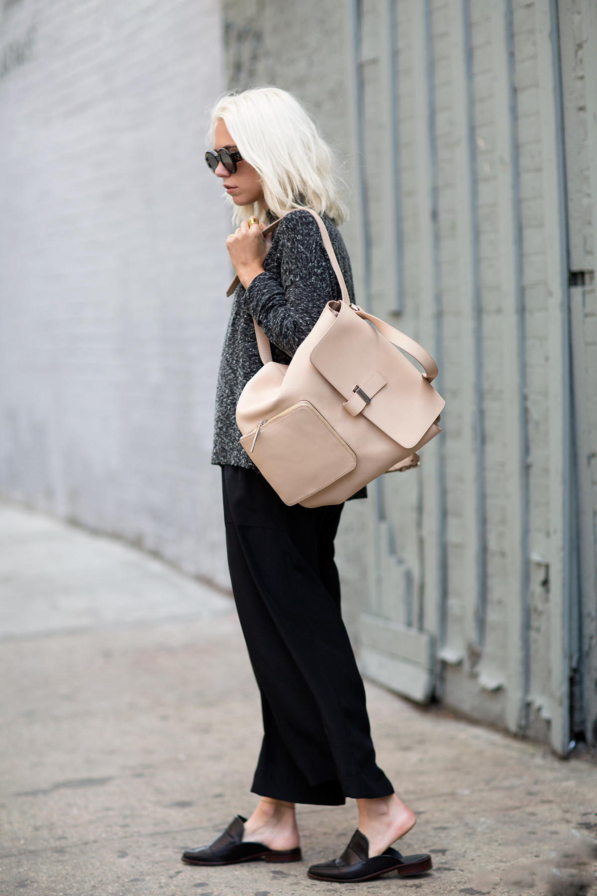 Courtney Trop showing of the a backpack from Whistles. Street Style September 2014