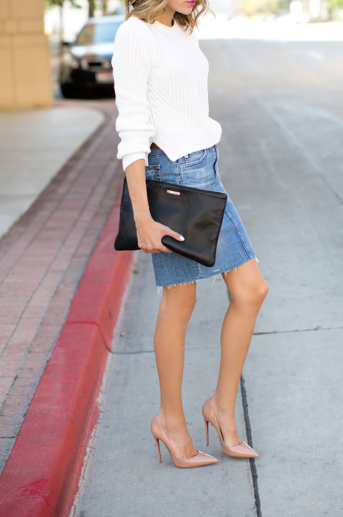 Christine Andrew is wearing a white crop sweater from H&M, denim skirt from Anthropologie, shoes from Christian Louboutin and oversized clutch from Saks Fifth Avenue