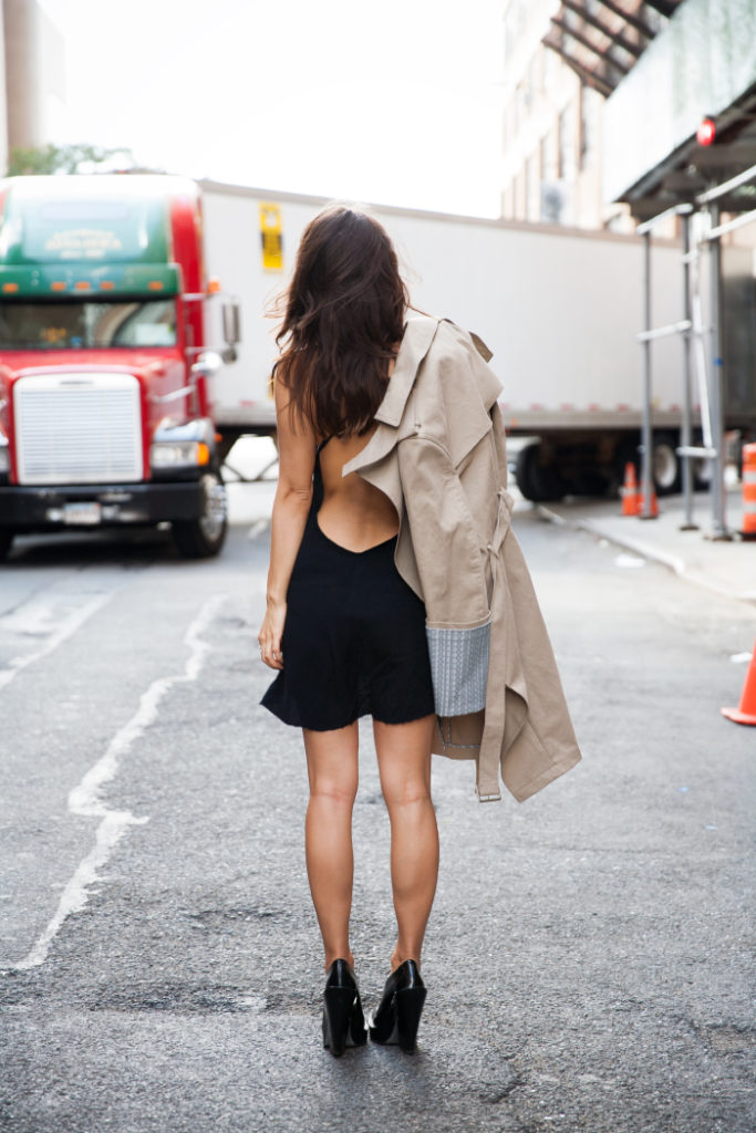 Rumi Neeley is wearing a black dress and a trenchcoat from Alexander Wang