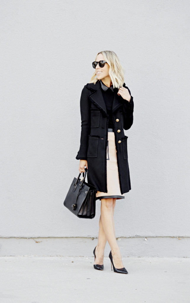 Jacey Duprie is wearing a knit coat from St. John Collection, skirt from Anjelica, sweater from Mackenzie, bag from Saint Laurent and shoes from Prada
