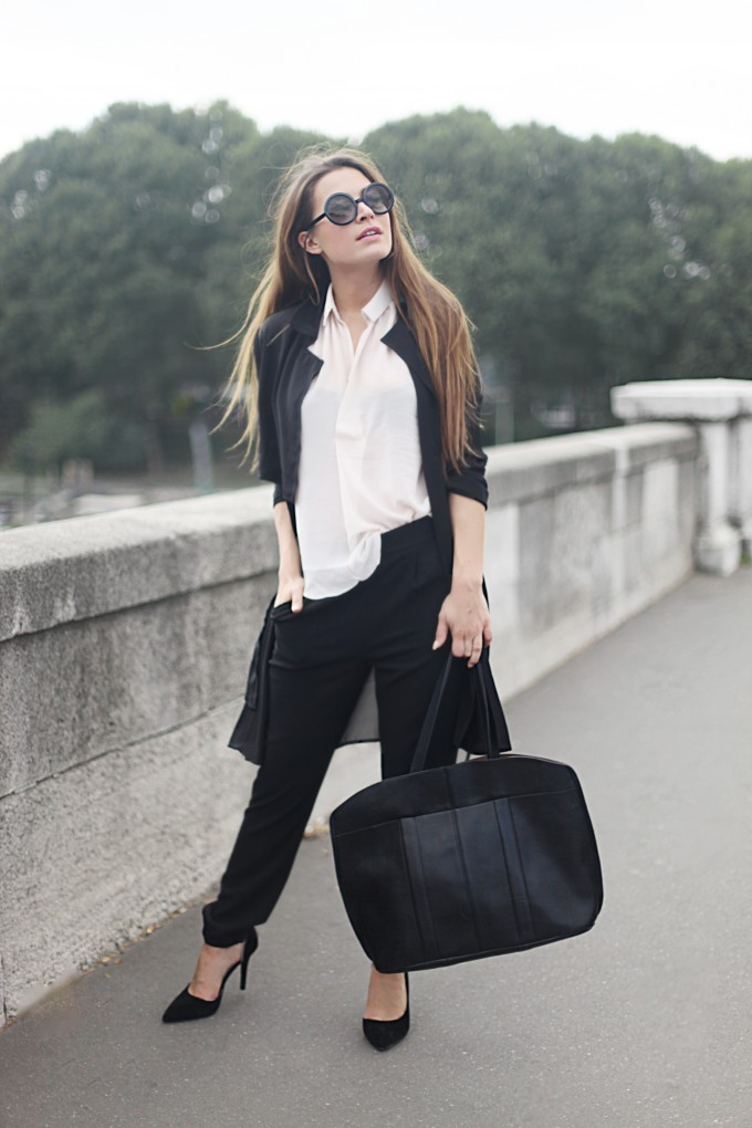 Audrey Leighton Rogers is wearing a black trench coat, blouse, joggers, shoes and weekend bag all from Boohoo