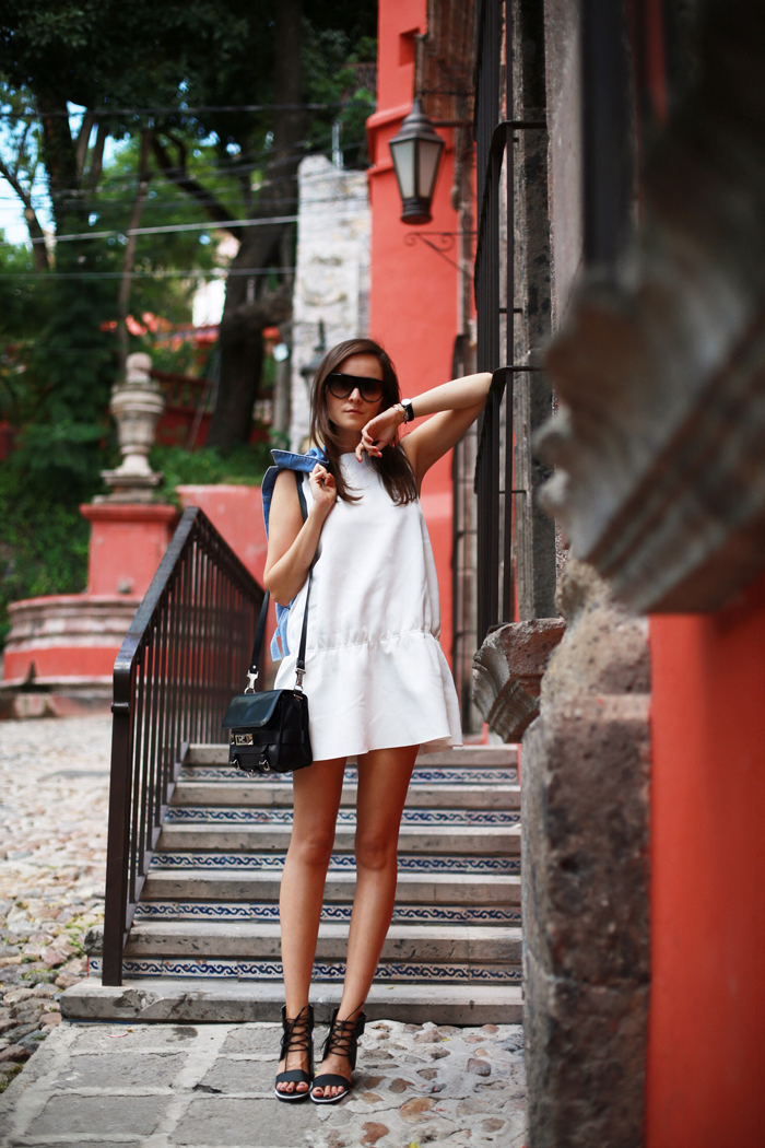 Andy Torres is wearing a white dress from H&N, sandals from Senso, sunglasses from Celine and the bag is from Proenza Schouler