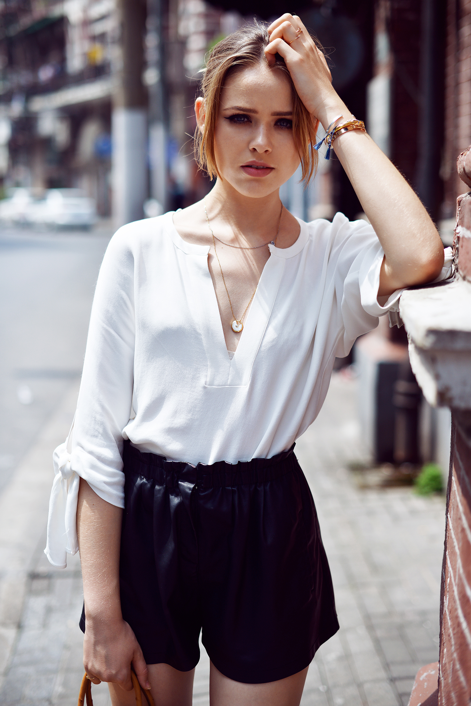Kristina Bazan is wearing a white top and black shorts from Zara