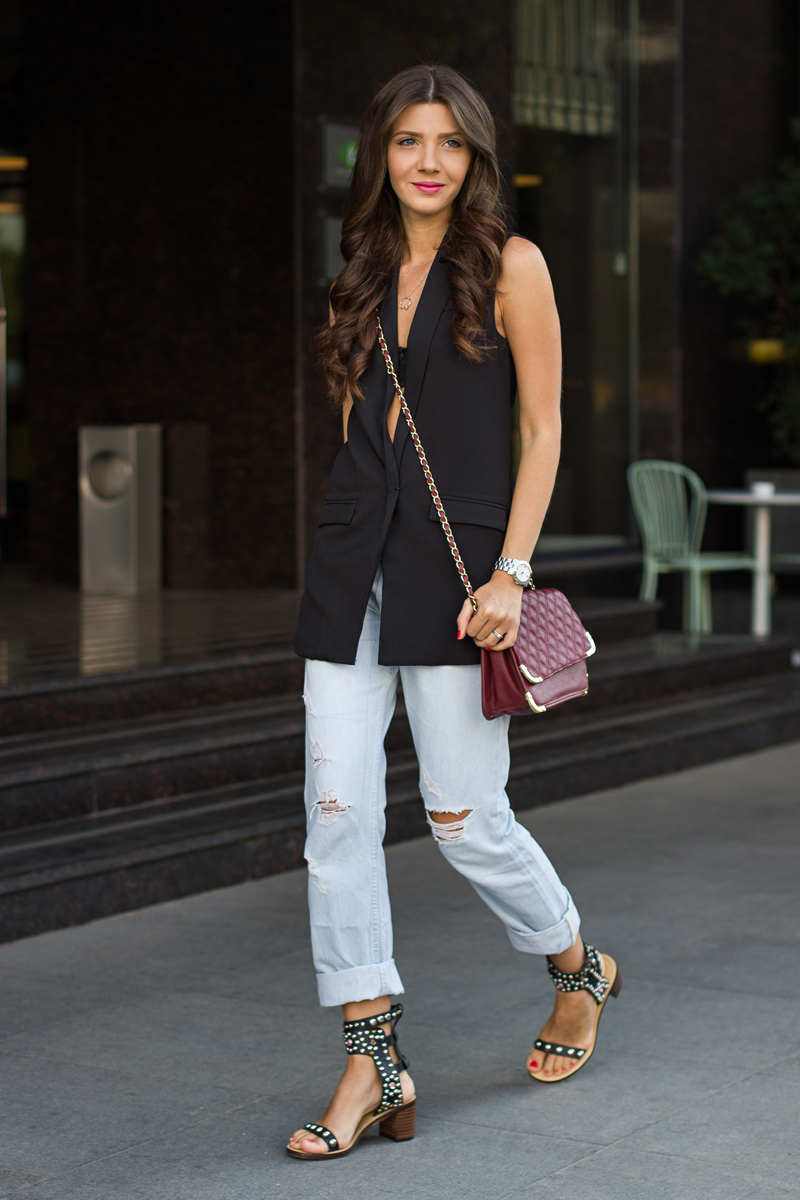 Larisa Costea is wearing a black vest from Sheinside, boyfriend jeans from Glow, shoes from Jessica Buurman and the bag is from Asos