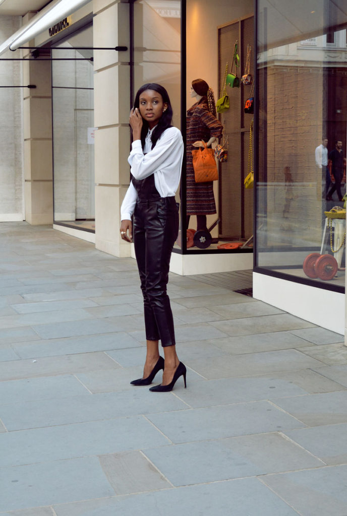 Natasha Ndlovu is wearing a white shirt from Asos and leather overalls from H&M