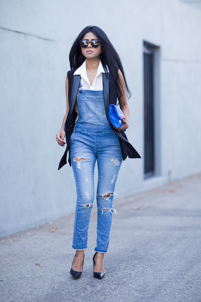 Sheryl Luke is wearing a black blazer vest from La Marque and worn denim overalls from Black Orchid