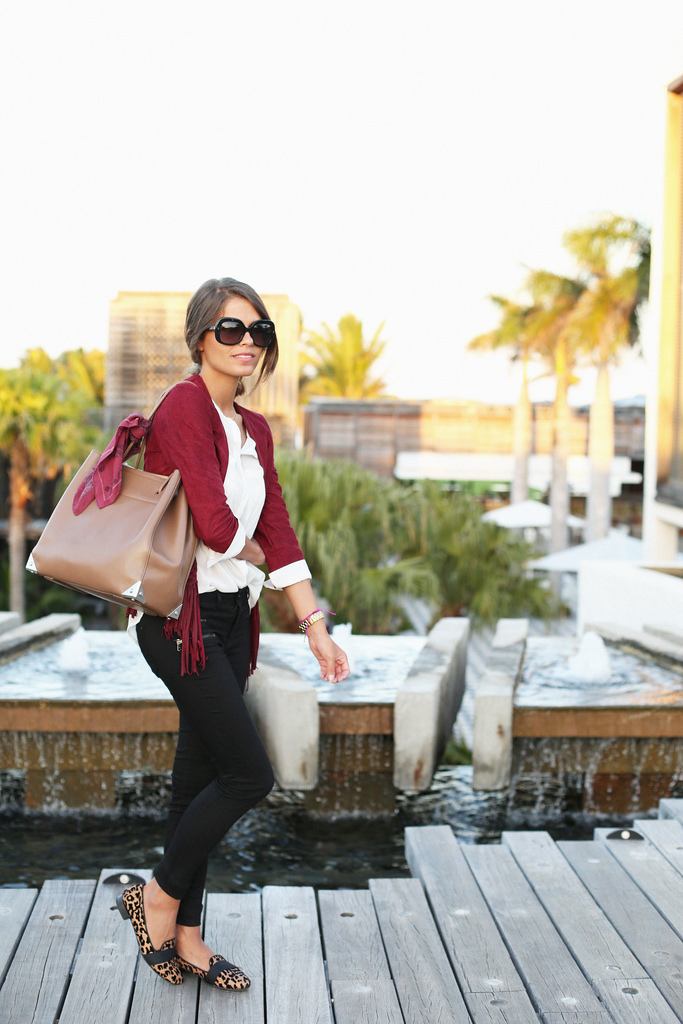 Jessie Chanes is wearing a fringed jacket in burgundy from Dresslux