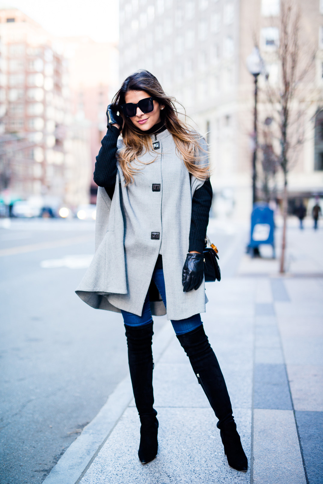 Pam Hetlinger is wearing a cape coat with thigh high boots and leather gloves, creating an overall stylish and glamorous look. Sunglasses are also a must have if the weather is good! Cape: Mango, Jeans: Topshop, Boots: Delamn, Bag: Gucci.