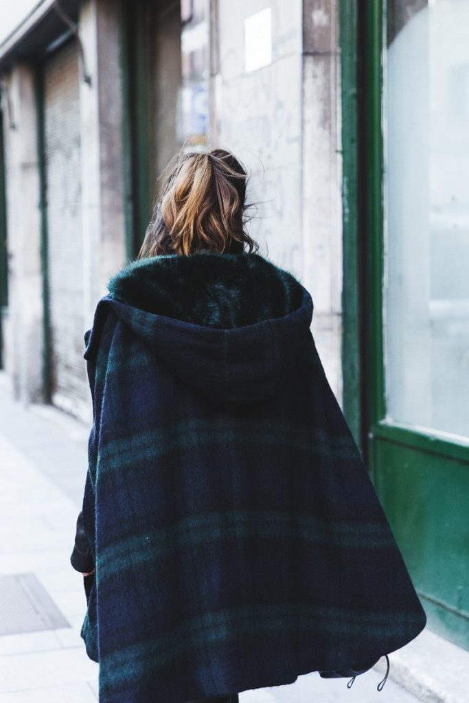 Sara Escudero is wearing a blue and green plaid cape from Zara