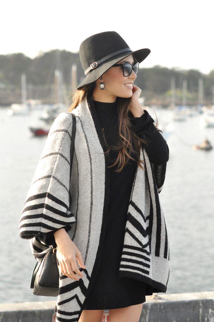 Jessica R. is wearing a grey and black cape from Zara