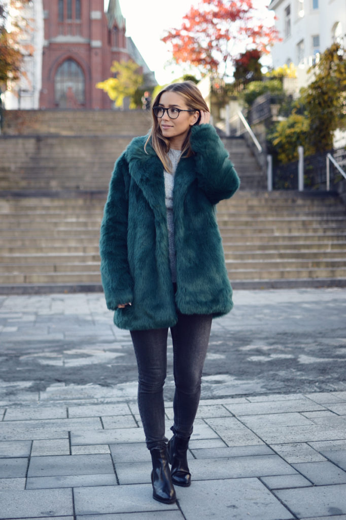 Emilie Tømmerberg wears an emerald fluffy coat with skinny jeans and Chelsea boots.   Coat: Nelly.com, Shoes: Vagabond.