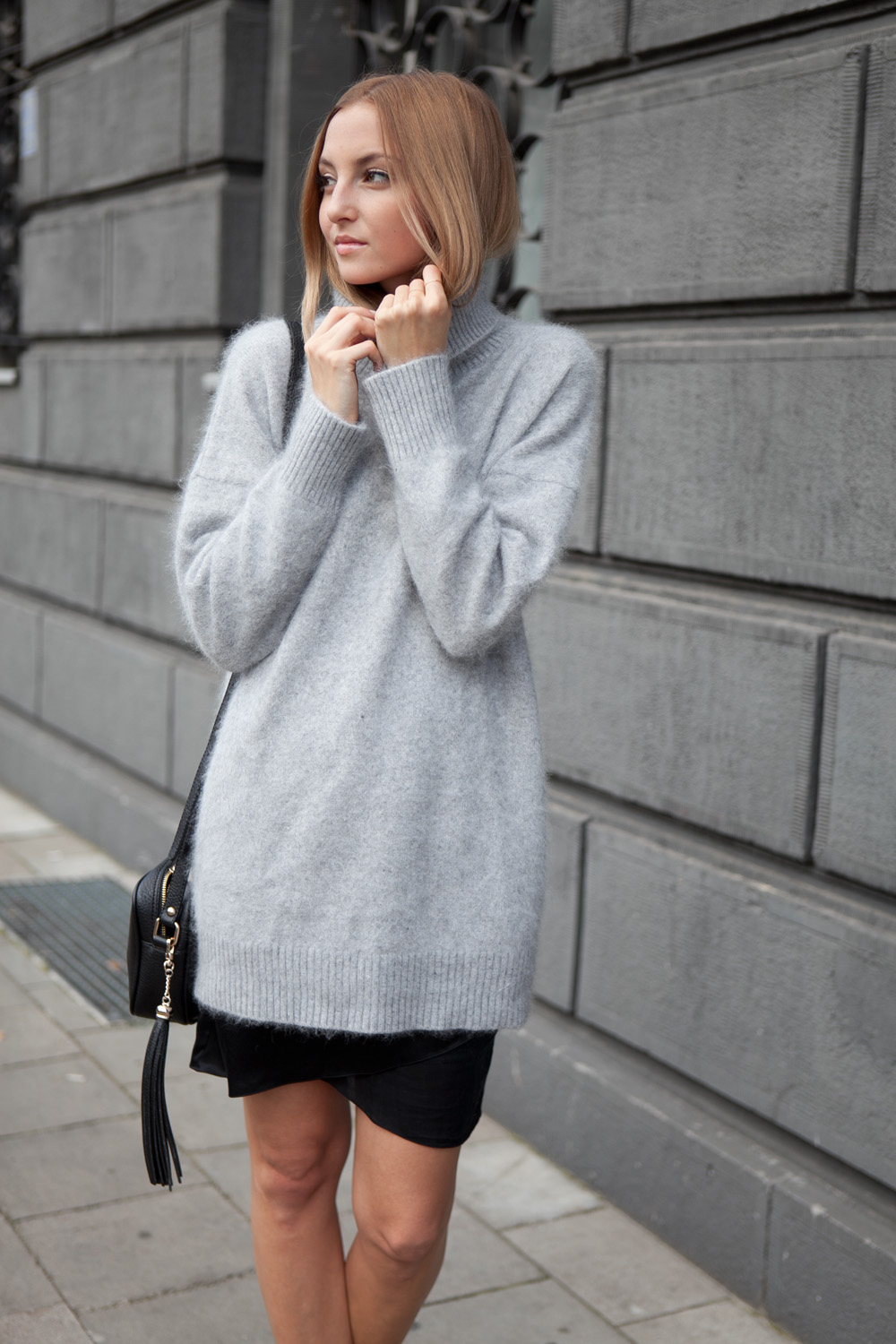 Jess A. is wearing a grey fluffy long sweater from Jessica Buurman