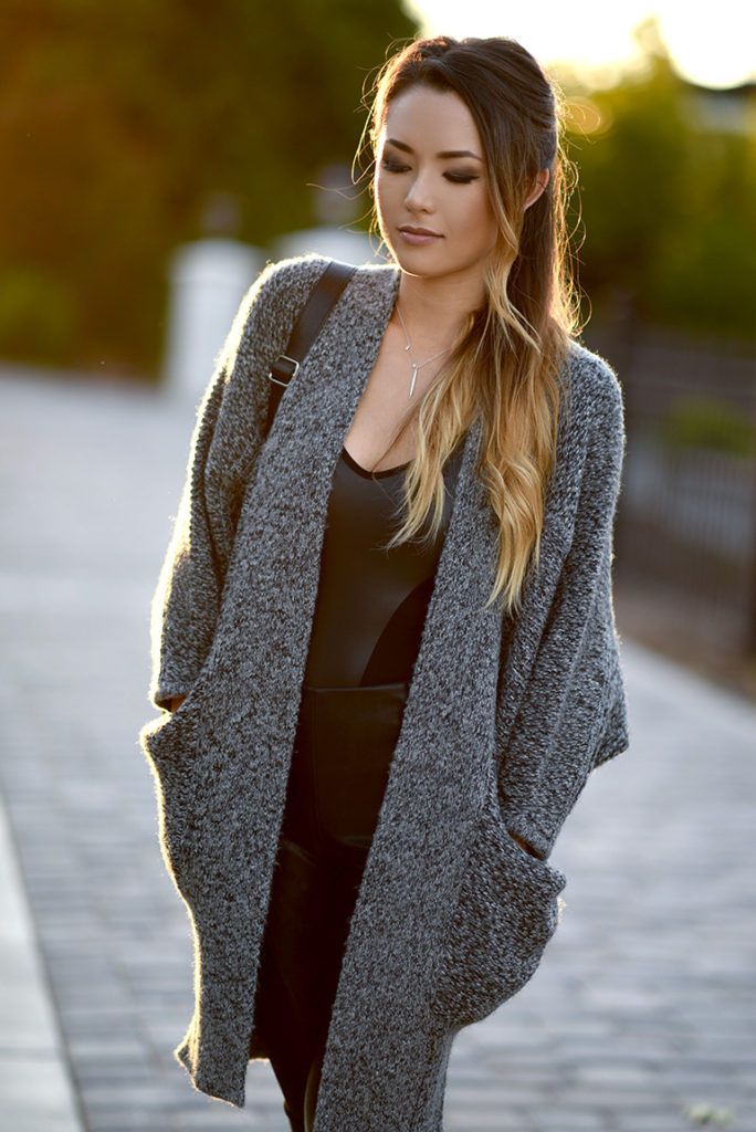 Long cardigans have never looked better. Jessica R. wears hers with a sheer black bodysuit.   Bodysuit/Cardigan: GUESS.