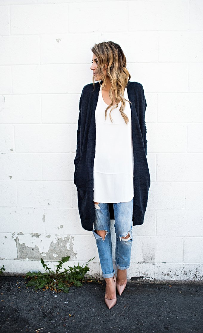 Christine Andrew wears a navy long cardigan with a classic white tee and distressed denim jeans. Cardigan: ILY Couture, Jeans: Nordstrom.
